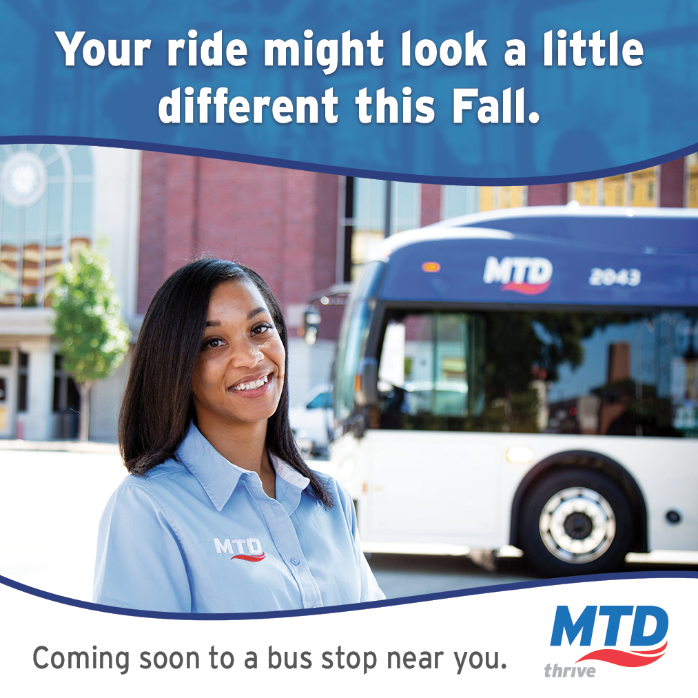 An MTD bus driver smiling and standing in front of a rebranded MTD bus.